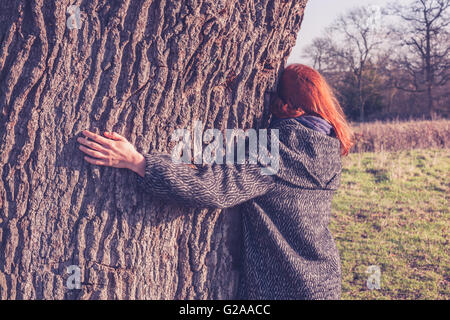 A young woman is hugging a big tree on a cold day of winter - Stock Photo