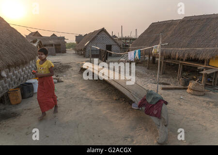 Young girl walking in a typical village, with houses and boats of fishermen, Mandalay, Myanmar, Burma, South Asia, - Stock Photo