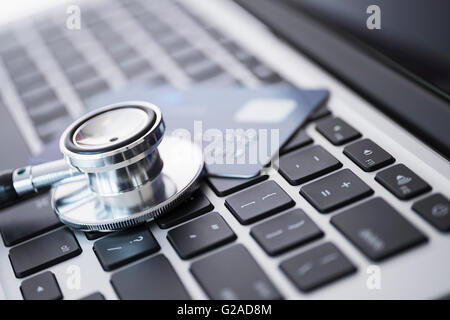 Stethoscope and credit card lying on laptop - Stock Photo