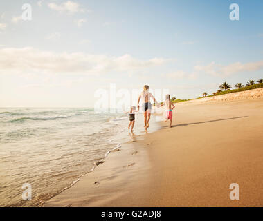 Mother running with boy (6-7) and girl (4-5) on beach by water - Stock Photo