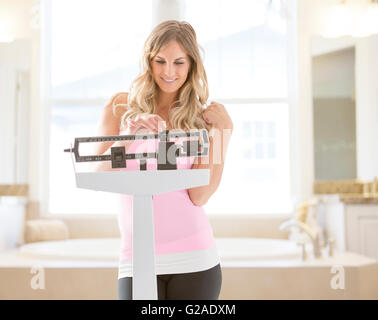 Young woman standing on weight scale in bathroom - Stock Photo