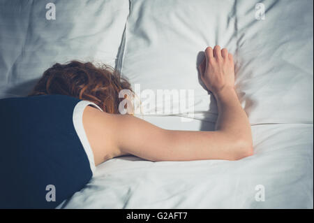 A young woman wearing a dress is passed out on a bed - Stock Photo