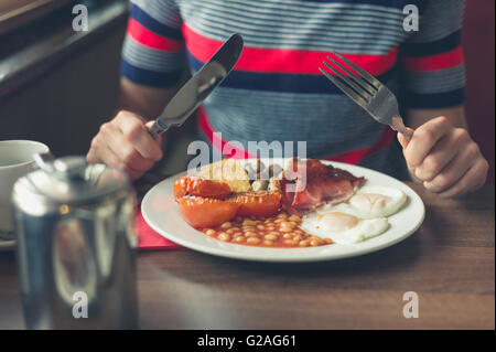 A young woman is having a traditional english breakfast in a diner - Stock Photo