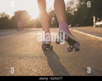 The legs of a young woman as she is roller skating in a park at sunset - Stock Photo