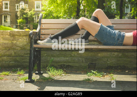A young woman is lying down and relaxing on a park bench on a sunny  summer day - Stock Photo
