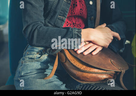A young woman is sitting on a train and is clutching a handbag - Stock Photo