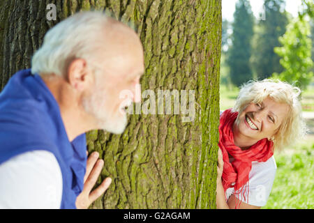 Happy senior couple playing hide and seek together in nature - Stock Photo