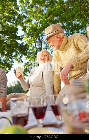 Happy senior people playing cards in a garden in summer - Stock Photo