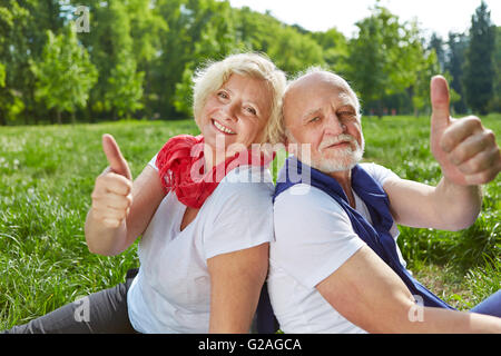 Happy old senior couple holding thumbs up in nature - Stock Photo