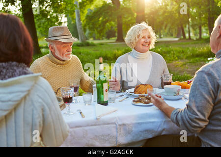 Happy family with seniors celebrating birthday in a garden in summer - Stock Photo