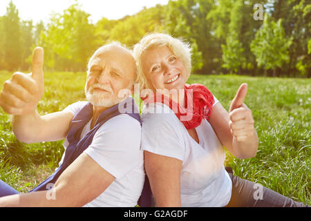 Happy senior couple holding thumbs up in summer vacation on a meadow - Stock Photo