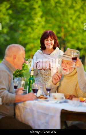 Happy senior friends celebrating birthday in a garden with cake and red wine - Stock Photo