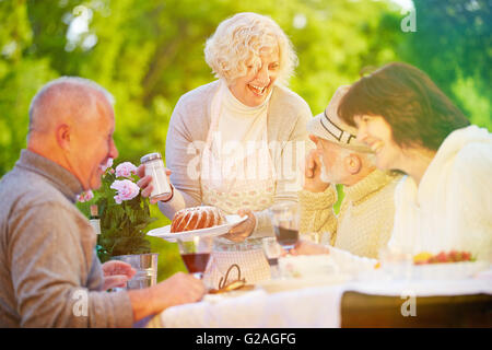 Friends and senior people celebrating birthday with cake at garden party - Stock Photo