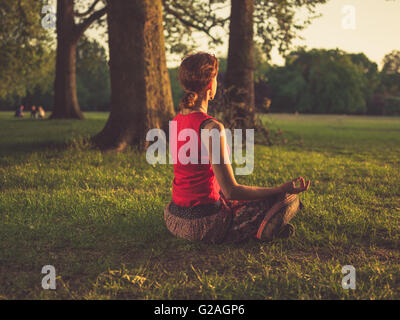 A young woman is sitting on the grass in a park and is meditating at sunset - Stock Photo
