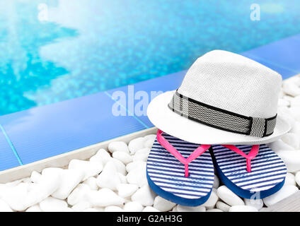 ... Flip Flops And Hat At The Pool On The White Gravel.   Stock Photo