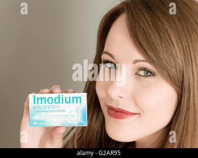 Portrait of a Woman Holding a Packet of Imodium Tummy Upset Tablets - Stock Photo