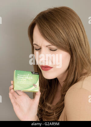 Portrait of a Woman Holding a Packet of Senna Pod Constipation Tablets - Stock Photo