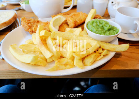 A plate of english fish, chips and mushy peas served on a plate in a restaurant - Stock Photo