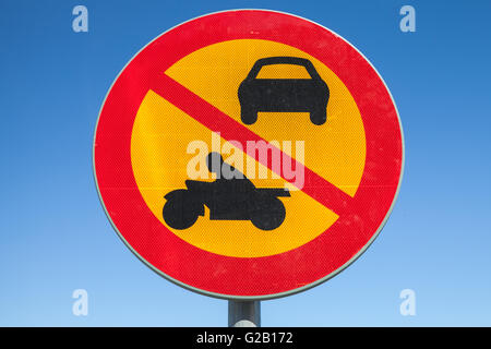 European round red and yellow traffic sign over blue sky, the passage of vehicles and motorcycles is prohibited - Stock Photo
