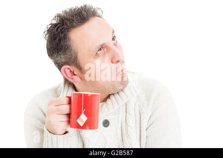 Cold man holding mug and  thermometer in mouth as flu or influenza concept - Stock Photo