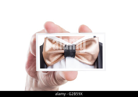 Hand holding card with golden leather bowtie picture as bow tie fashion concept - Stock Photo