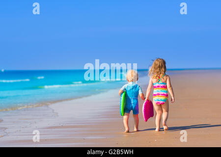 Happy child running and jumping in the waves during summer vacation on exotic tropical beach. Holiday on ocean coast - Stock Photo