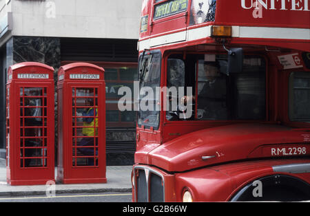 Great Britain London, red telephone cabin of british telecom and red double decker bus - Stock Photo
