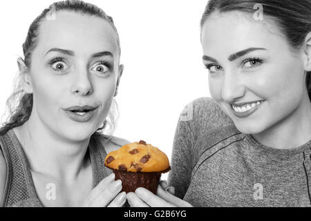 two woman dressed in fitness clothes getting excited about to eat a muffin - Stock Photo