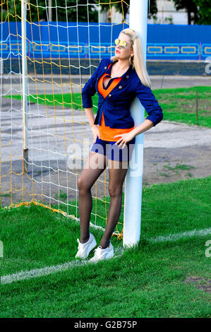 the beautiful woman in gate of a football field - Stock Photo