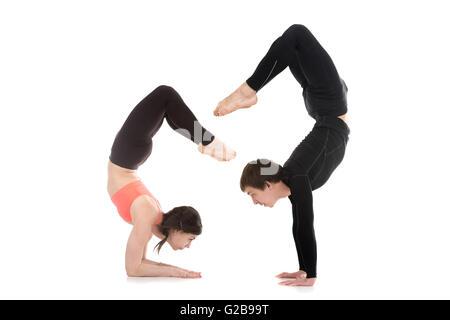 Profile of two sporty people doing handstand, balance exercises, yogi couple standing in yoga asana Scorpion Pose - Stock Photo