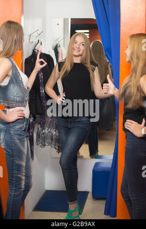 Group of three girlfriends shopping together. Happy smiling young beautiful woman wearing jeans standing in fitting - Stock Photo