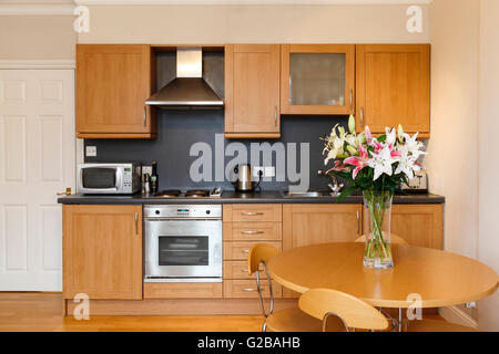 Molyneux House, Marble Arch. Modern small kitchen layout with dining table. Glass vase with flowers on table. Wood - Stock Photo