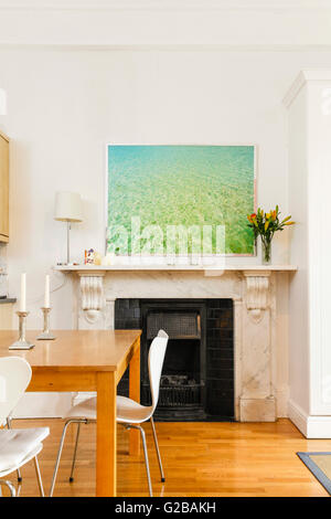 Pembridge Square, Notting Hill. View of a modern painting above a fireplace. Partial view of a wood dining table - Stock Photo
