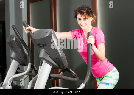 Beautiful athletic woman doing cardio exercises on stepper as resistance concept - Stock Photo