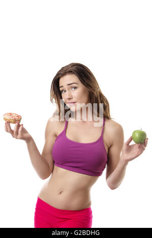 Slim fitness model deciding if she should eat the doughnut in her right hand or the apple in her left hand - Stock Photo