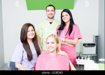 Team of young dentists and happy satisfied female patient - Stock Photo