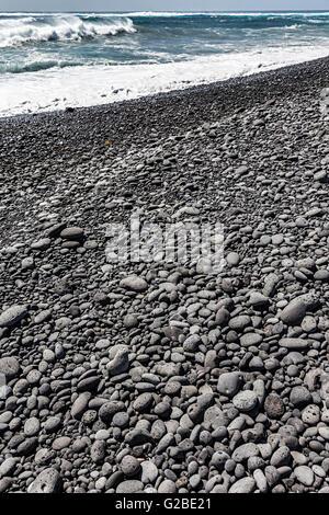 Worn black volcanic rock pebbles on beach, Playa Janubio, Lanzarote, Canary Islands, Spain - Stock Photo