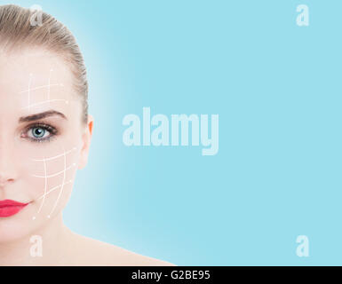 Close-up portrait of half face of young, beautiful woman ready for plastic surgery treatment - Stock Photo