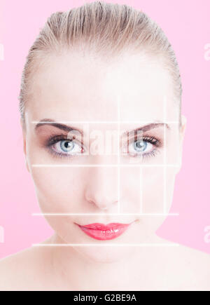 Close-up of beautiful woman face with makeup and divided lines as anti-aging and face lifting concept against pink - Stock Photo
