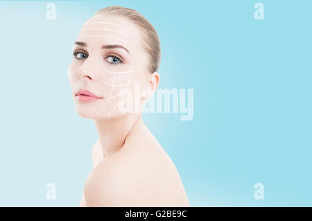 Beautiful woman with arrows on her perfect retouched face as cosmetic surgery concept against blue background - Stock Photo