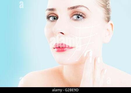 Close-up of female with makeup preventing wrinkles by using face cream on blue background - Stock Photo