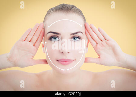 Beautiful smiling woman face ready for cosmetic surgery against orange or yellow background - Stock Photo