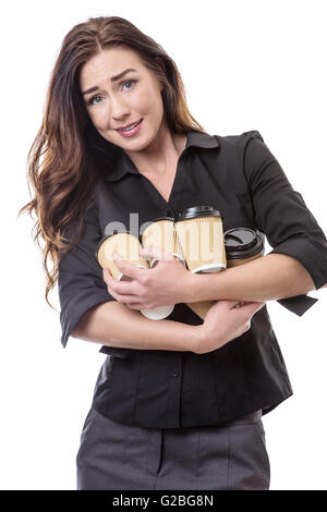 Close up shot of a pretty brunette business woman juggling some takeaway cups isolated on white - Stock Photo