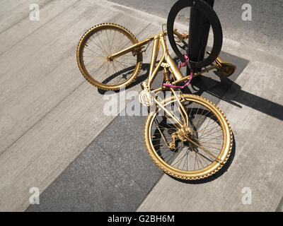 Bicycle painted with golden color chained to a post, Canada - Stock Photo