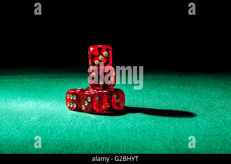 Red dice on green and black background - Stock Photo