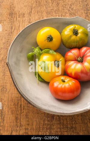 Multicolored heirloom tomatoes and basil in a ceramic bowl on a rustic wooden surface. - Stock Photo