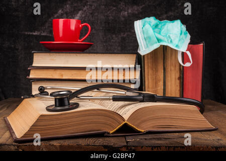 Stethoscope on open book and coffee on books pile - Stock Photo