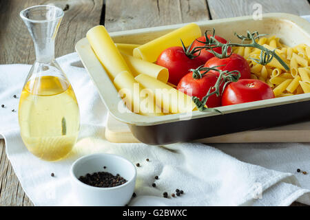 Pasta, raw tomatoes, olive oil selective focus - Stock Photo