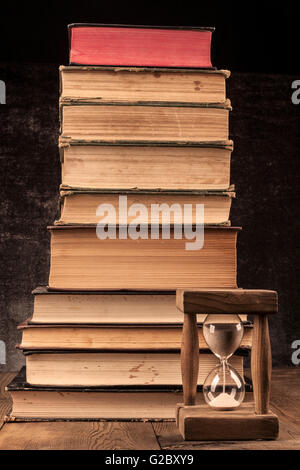 Old Books Pile on Wood Table with Hourglass and Dark Background - Stock Photo