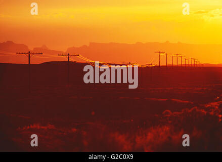 TELEPHONE & ELECTRIC POWER LINES AT SUNSET IN SOUTHERN UTAH; USA - Stock Photo